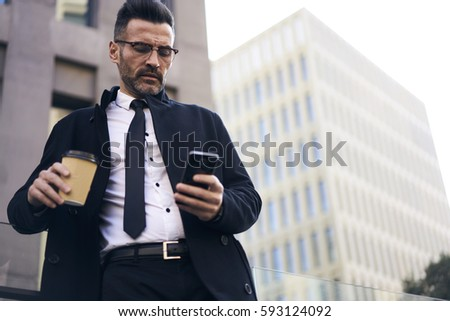 Well-dressed handsome mature business man making online booking of airline tickets arranging meeting with foreign partners using smartphone and 5G wireless making payments online during coffee break