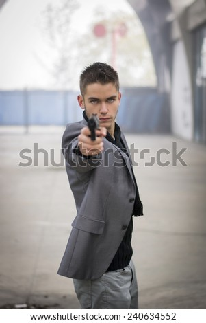 Well dressed handsome young detective or policeman or mobster standing in an urban environment aiming a firearm directly to the camera with a determined expression, front view - stock photo