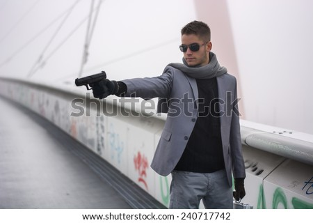 Well dressed handsome young detective or policeman or mobster standing in an urban environment aiming a gun to left side - stock photo