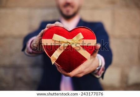 Well-dressed man with smile giving a red heart shape Valentine's gift towards the camera - stock photo