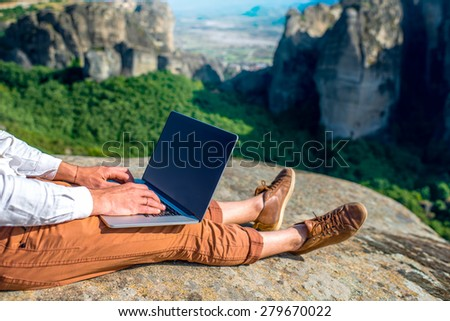 Well-dressed man working with laptop sitting on the rocky mountain on beautiful scenic clif background. Close up view with no face focused on laptop with hands - stock photo