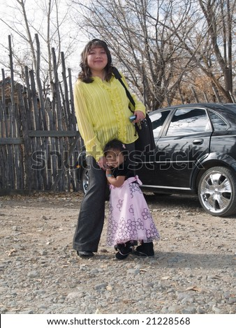 Well dressed Native American woman with a laptop standing by her car and holding her daughter's hand. In the background a traditional latilla fence. - stock photo