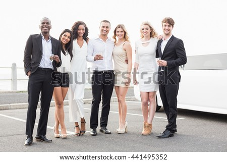 Well dressed people posing next to a limousine on a night out - stock photo