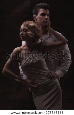 Well-dressed retro couple on dark wooden background - stock photo