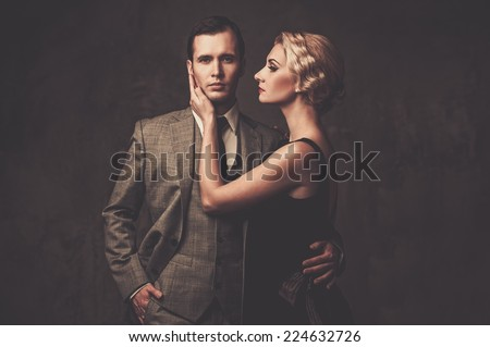 Well-dressed retro couple on grey background
