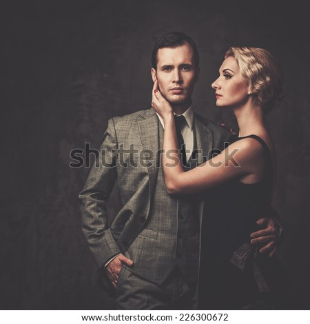 Well-dressed retro couple on grey background - stock photo