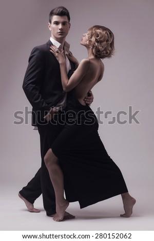 Well-dressed retro couple over grey studio background - stock photo