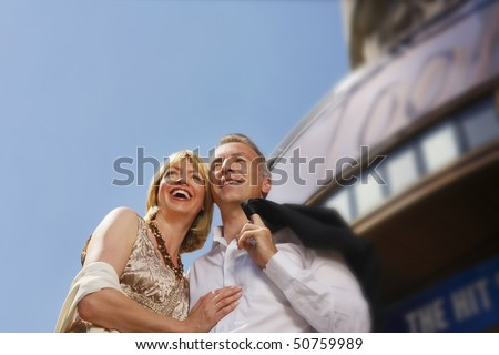 Well dressed smiling couple standing by building outdoors, low angle view - stock photo
