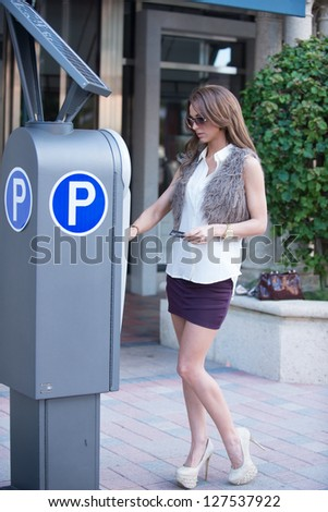 Well dressed women at a parking meter - stock photo