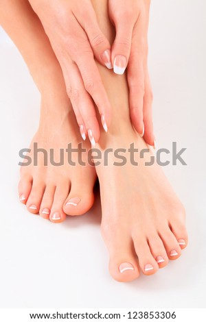Well-groomed hands on female feet - stock photo