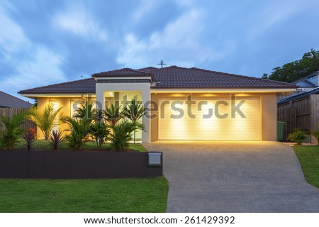 Well lit modern home exterior at dusk - stock photo