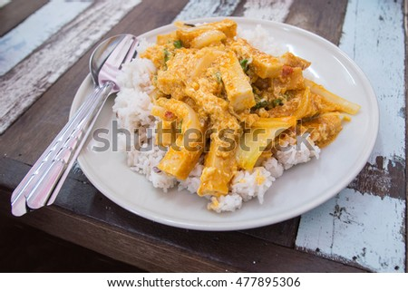 Well steamed rice with curry fried Vietnamese pork sausages with scrumbled egg on top, in a white ceramic dish on a wood table