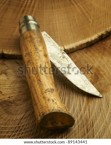 Well used pocketknife with rough wooden handle and blade with scrapes from use resting on natural slices of wood. - stock photo