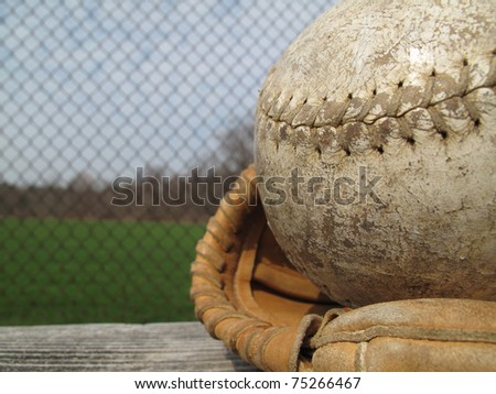 Well used softball and catcher's mitt with shallow depth of field - stock photo