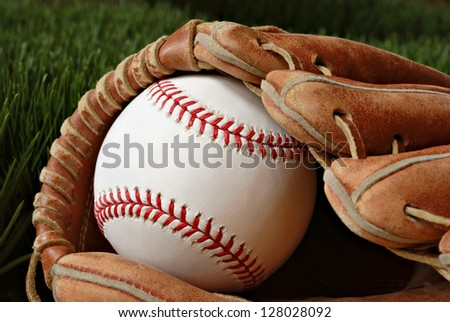 Well worn baseball glove with new ball on grass. Highly detailed closeup image taken in soft side-lighting to emphasize stitching and texture of baseball.  Shallow dof. - stock photo