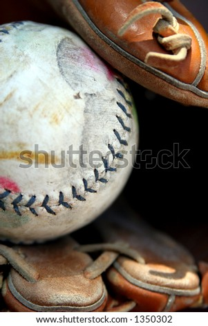 Well-worn softball in glove, long. - stock photo