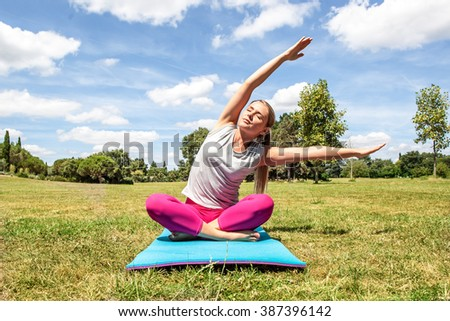 wellbeing and stretching outside - relaxed young blond woman doing yoga with bent upper body on exercise mat over summer blue sky - stock photo