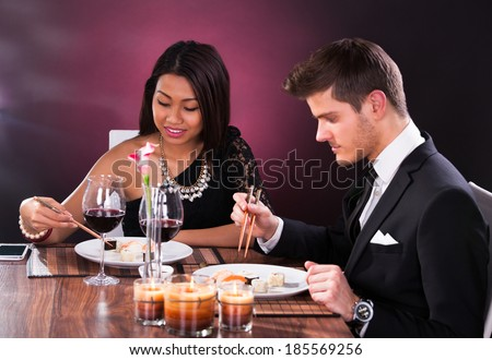 Welldressed young couple having meal at restaurant table - stock photo