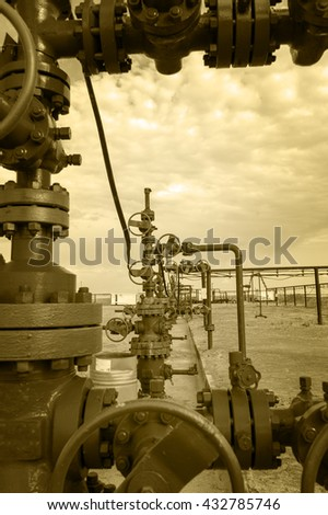 Wellhead with valve armature. Oil, gas industry. Toned sepia.