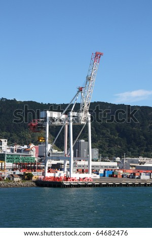 Wellington, capital city of New Zealand. Harbor crane and container crates. - stock photo