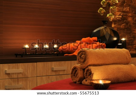 Wellness and spa concept with candles, collection of towels and part of massage table. - stock photo
