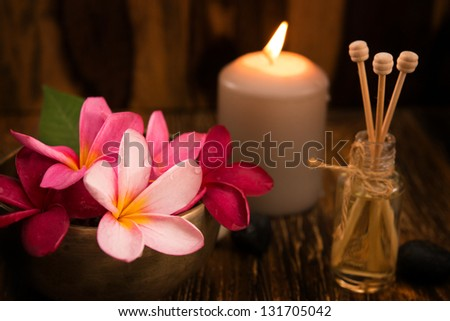 Wellness and spa concept with candles, frangipani flower, sandalwood and rattan sticks on massage table. - stock photo