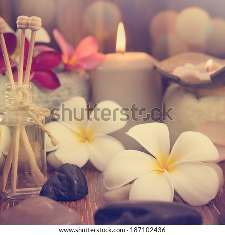 Wellness and spa concept with candles, frangipani flower, sandalwood and rattan sticks on massage table in vintage retro style. - stock photo