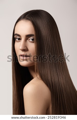 Wellness and spa. Sensual woman model with straight dark hair. Shiny long health hairstyle. Beauty and haircare. Natural look with naturel makeup, strong eyebrows, clean skin