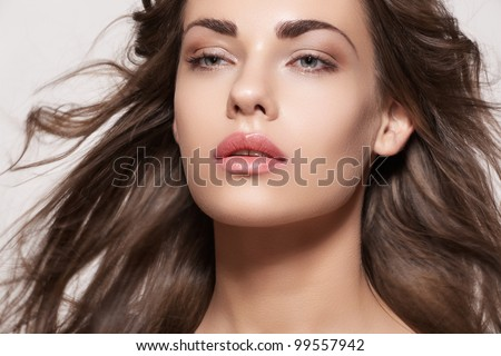 Wellness and spa. Sensual woman model with windswept flying brunette hair on light gray background. Shiny long health hairstyle. Beauty and haircare. Natural fashion make-up - stock photo