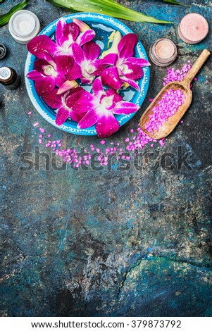 Wellness or spa background with pink orchid flowers  in bowl with water, shovel of sea salt, cream jar , candles and green bamboo leaf . Top view, place for text. - stock photo
