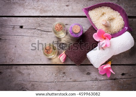 Wellness or spa  setting. Bottles with aroma oil, sea salt, towels  and  pink plumeria on vintage wooden background. Selective focus. Place for text. - stock photo