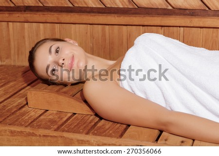 Wellness practice. Close-up of a young woman in white towel smiling at a camera while she lies in sauna - stock photo