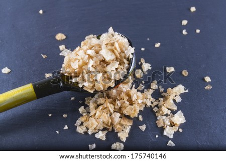 Welsh oak smoked sea salt flakes on a wooden spoon with a dark slate background. The salt is from Anglesey, Wales, United Kingdom, granted EU protected status in 2014. Close up. - stock photo