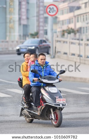 WENZHOU-CHINA-NOVEMBER 17, 2014. Couple with kid on electric scooter. China has 200 million e-bikes running on the road, a tenfold increase from 2005. They are manufactured by 700 Chinese companies.