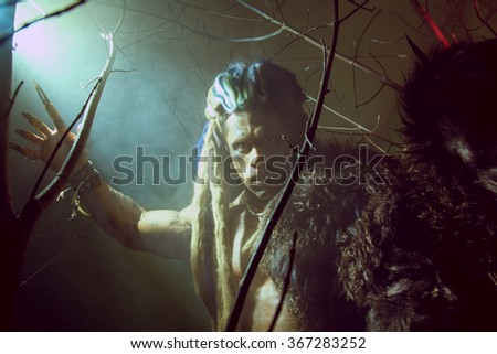 Werewolf with long nails and crooked teeth among the branches of the tree and smoke. Gothic image of scary diabolical creatures for Halloween - stock photo