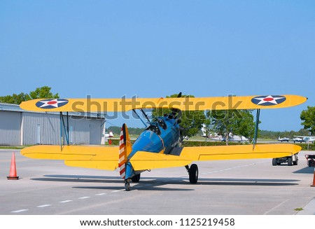WEST PALM BEACH, FLORIDA - June 14, 2009:A Boeing Stearman blue and yellow world war II American trainer aircraft parked on an airport ramp