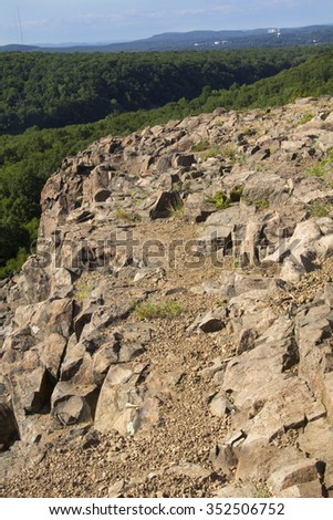 West ridge and cliffs of Ragged Mountain, along the Metacomet Trail in Berlin, Connecticut. Volcanic rocks typical of the Metacomet Ridge are in the foreground. Vertical image. - stock photo