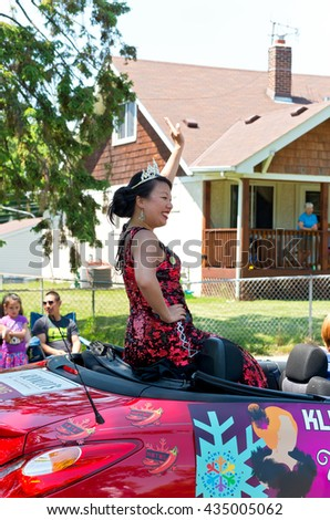 WEST ST. PAUL, MINNESOTA - MAY 21, 2016: Princess of South Wind for St. Paul Winter Carnival Peggy Ly waves to crowd at Grande Parade in West St. Paul on May 21.  - stock photo