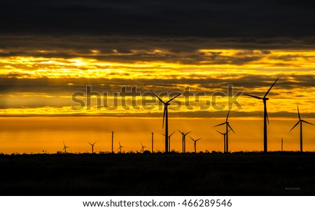 west texas wind turbine farm at sunrise producing clean renewable energy day and night turbines on the right side of shot