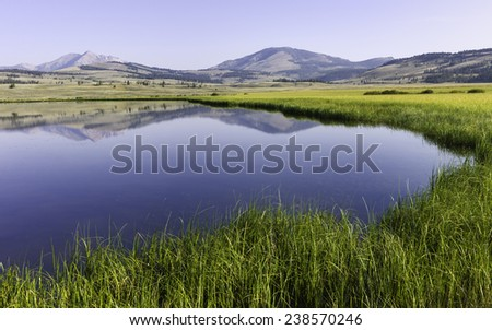 West Yellowstone, Wyoming, USA - Reflections of hills, trees, snow peaked mountains on a bring sunny day in Yellowstone National Park near West Yellowstone, Wyoming, USA. - stock photo