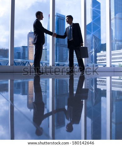 Western and Chinese Businessmen Shaking Hands in Hong Kong - stock photo