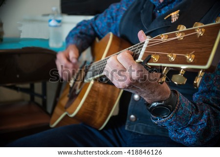 Western cowboy playing guitar - stock photo