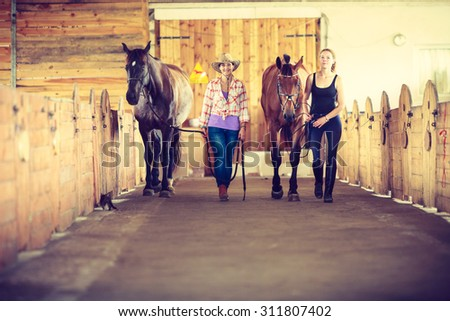 Western cowgirl and young woman walking with horses in stable paddock. Instagram filter. - stock photo
