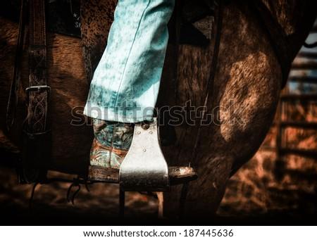 Western cowgirl boot in stirrup on horse in darker portrait - stock photo
