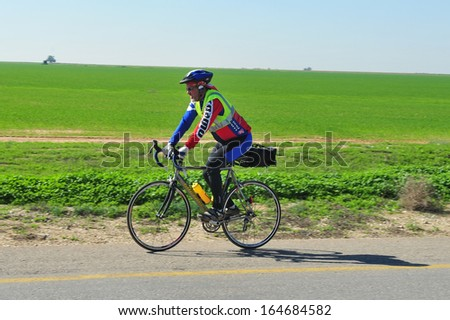 WESTERN NEGEV ISR - FEB 18:Cyclist riding a bike on an open road on Feb 02 2011.On a bicycle you can travel up to 1037kms on the energy equivalent of a single litre of petrol.