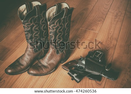 Western Wear Boots and Gun in Holster. Pair of old western cowboy boots and a revolver in a holster sitting on a hardwood floor.