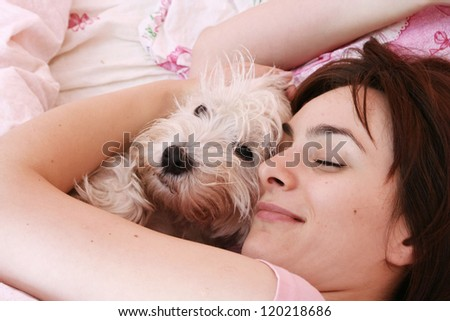 Westie sleeping next to woman in bed .
