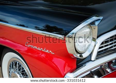 WESTLAKE, TEXAS - OCTOBER 17, 2015: Red and black 1956 Studebaker Commander Sedan classic car. Closeup of headlight details. - stock photo