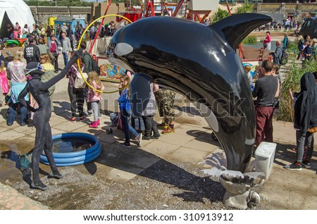 WESTON-SUPER-MARE, UK - AUGUST 26, 2015:  A queue of visitors to the parody theme park Dismaland snakes past a sculpture involving a performing orca whale.