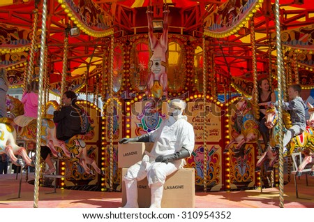 WESTON-SUPER-MARE, UK - AUGUST 26, 2015:  An abattoir worker resting on a box of carousel horsemeat lasagne, Dismaland.  The Banksy inspired parody of a theme park has attracted thousands of visitors. - stock photo